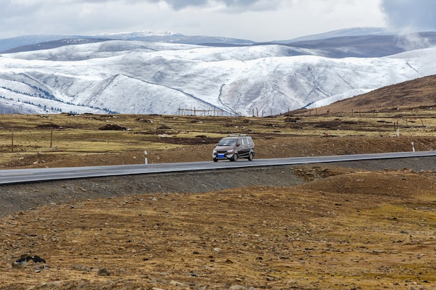 Van car en el camino, hermoso camino de invierno en el tíbet bajo la montaña de nieve sichuan, china