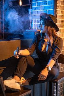 Vaping muchacha hermosa joven que fuma el cigarrillo electrónico en club.