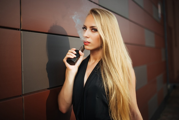 Vaping. mujer hermosa joven que fuma el e-cigarrillo con humo al aire libre.