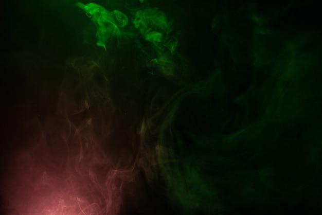 Vapor verde y rosa sobre una superficie negra