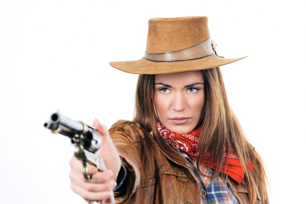 Vaquera atractiva con pistola sobre fondo blanco.