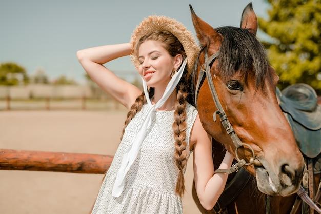 Vaquera de campo con un caballo en una granja