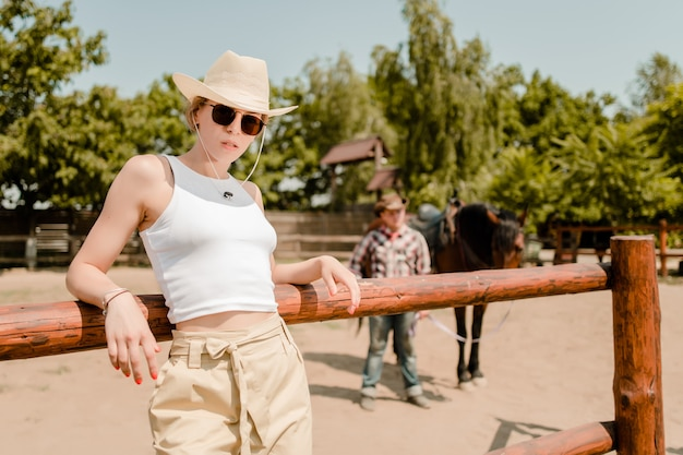 Vaquera en un sombrero con vaquero y caballo en el fondo