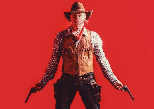 Vaquero con arma sobre fondo rojo. bandido americano en máscara, hombre occidental con sombrero. granjero o vaquero con sombrero. hombre vestido con sombrero de vaquero, pistola. oeste, armas.