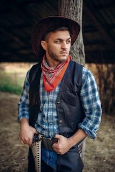 Vaquero brutal en jeans y chaqueta de cuero, rancho de texas, western. persona del sexo masculino vintage con revólver, estilo de vida del salvaje oeste