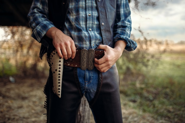 Vaquero en jeans y ropa de cuero con la mano en el revólver