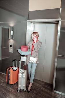 Vaqueros y chaqueta. mujer elegante vestida con jeans y chaqueta llamando al taxi mientras está de pie cerca del ascensor
