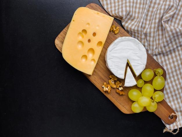 Variación de queso, nueces y uvas en tabla de cortar de madera. queso camembert y queso edam. comida para vino y romántica, desde la vista superior.