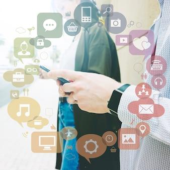 Varias aplicaciones formando círculo en frente de dos personas que usan el teléfono móvil