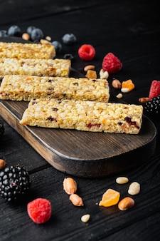 Varias barras de cereales, muesli y granola saludables, sobre mesa de madera negra