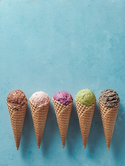 Varias bolas de helado en conos con espacio de copia. colorido helado en conos de chocolate, fresa, arándano, pistacho o matcha, galletas galletas sandwich de chocolate sobre fondo azul. vista superior