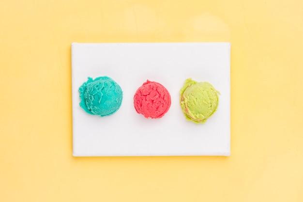 Varias bolas de helado en tablero blanco