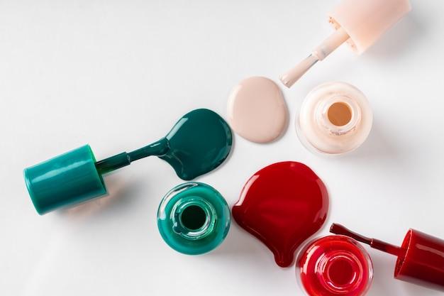 Varias botellas abiertas de esmalte de uñas sobre fondo blanco.