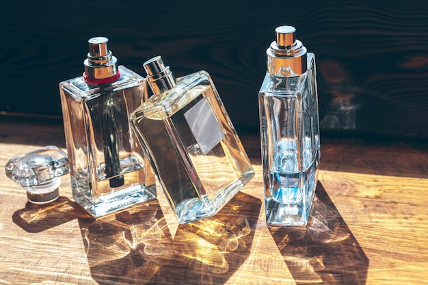 Varias botellas con perfume en rayos de sol sobre mesa de madera