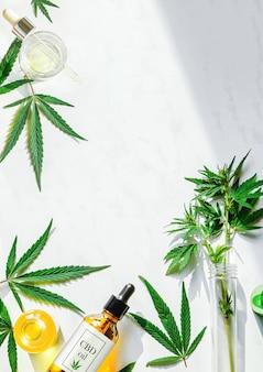 Varias botellas de vidrio con aceite de cbd, tintura de thc y hojas de marihuana sobre una canica