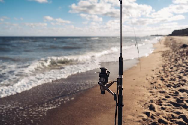 Varias cañas de pescar en una fila en la playa