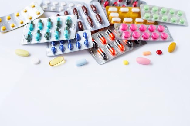 Varias cápsulas de medicamentos, píldoras y tabletas en blister en blanco