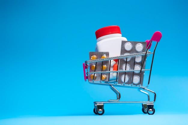 Varias cápsulas, paquete de tabletas y medicamentos en el carrito de la tienda.