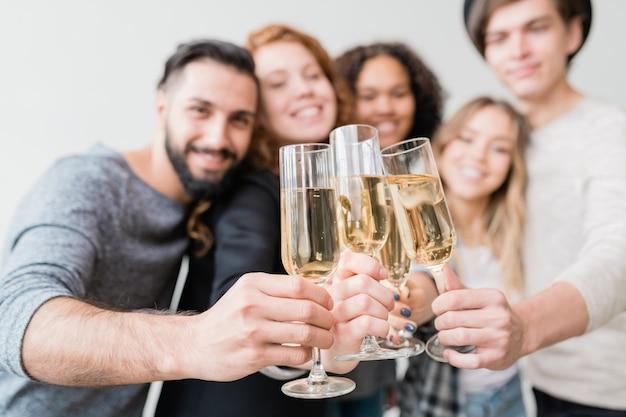 Varias copas con champán espumoso sostenidas por un grupo de jóvenes amigos alegres durante el brindis por año nuevo