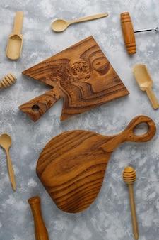 Varias cucharas de madera con tabla de cortar de madera hecha a mano sobre hormigón gris