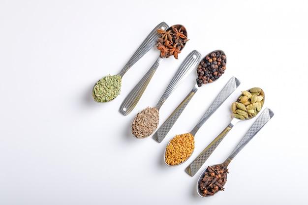 Varias especias en cucharas sobre fondo blanco