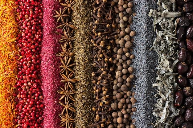 Varias especias y hierbas se encuentran dispersos en la mesa. backg de condimento