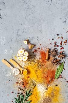 Varias especias en polvo (pimentón, curry, cilantro, jengibre, cebollas secas y ajo, cúrcuma, canela, pimienta, anís) y hierbas.