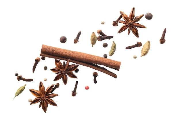 Varias especias voladoras para hacer té masala aislado sobre superficie blanca