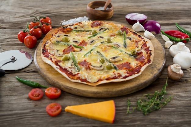 Varias especies con pizza dispuestas en bandeja de madera.