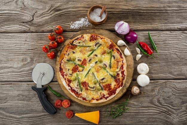 Varias especies con pizza y tomate en una bandeja de madera.