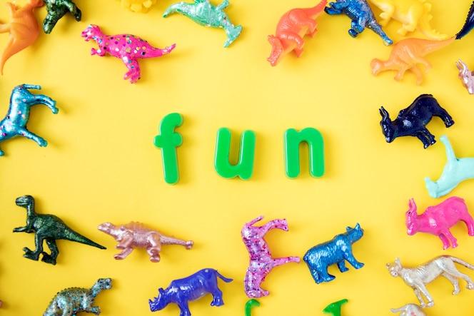 Varias figuras de juguete de animal de fondo con la palabra diversión