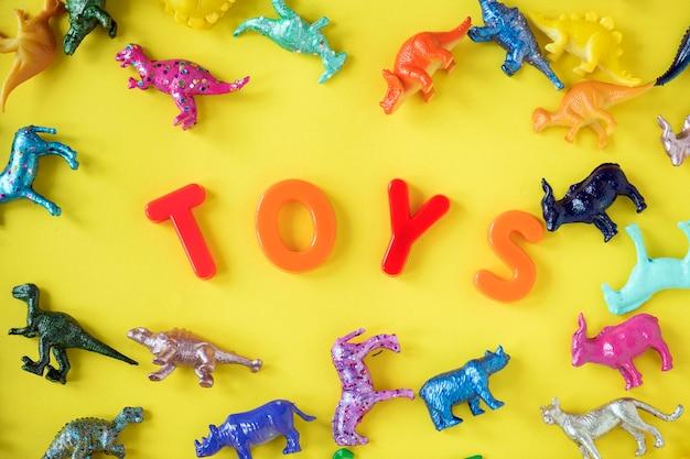 Varias figuras de juguete de animal de fondo con la palabra juguetes