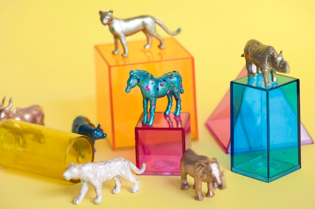 Varias figuras de juguete de animales con cajas y en un fondo colorido.