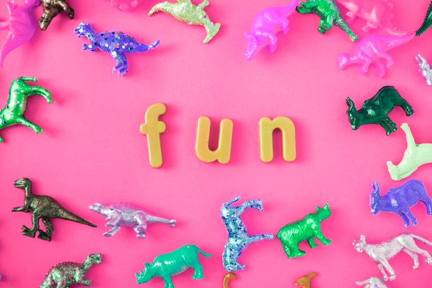 Varias figuras de juguete de animales de fondo con la palabra diversión