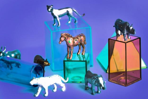 Varias figuras de juguetes de animales con cajas y en un fondo colorido