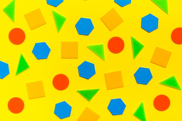 Varias figuras planas (círculos, triángulos, cuadrados, hexágonos) se encuentran abstractamente sobre cartón amarillo. colores de fondo brillante.