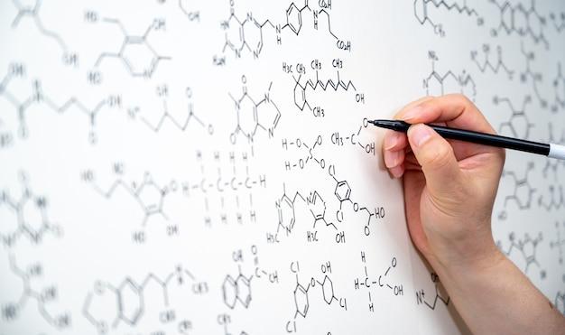 Varias fórmulas químicas están escritas en la pizarra. antecedentes del concepto científico.