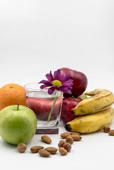 Varias frutas; avellana; almendra con vaso de agua y flor en fondo blanco