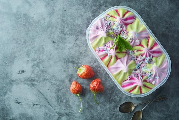 Varias frutas y bayas de helado en caja de plástico.