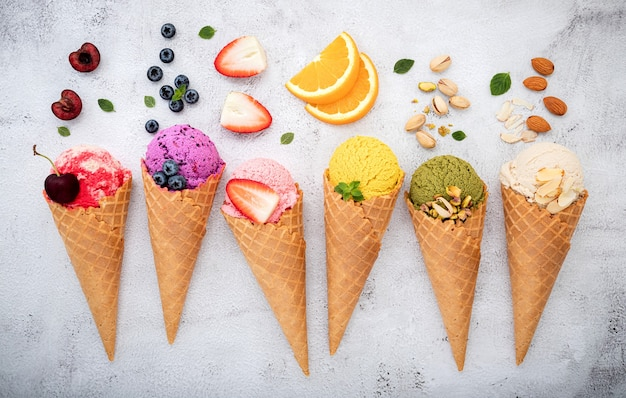 Varias frutas en conos sobre fondo de piedra blanca.