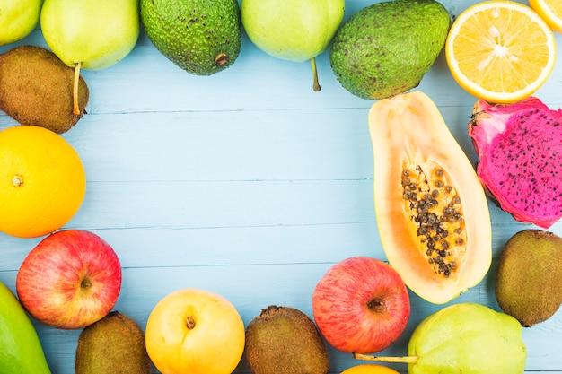Varias frutas frescas en la parte superior de la tabla de madera azul