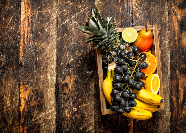 Varias frutas maduras en una caja de madera sobre mesa de madera.