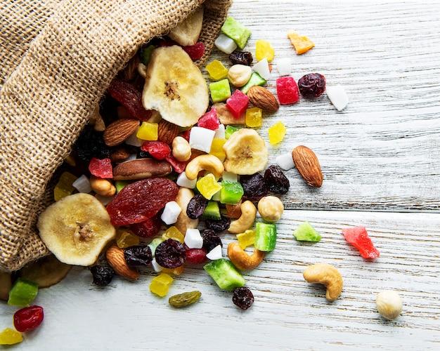 Varias frutas secas y nueces de mezcla sobre una mesa de madera blanca.