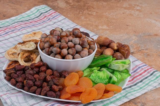 Varias frutas secas y nueces en un plato blanco.