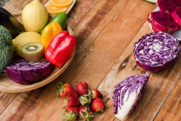 Varias frutas con verduras sobre fondo de madera