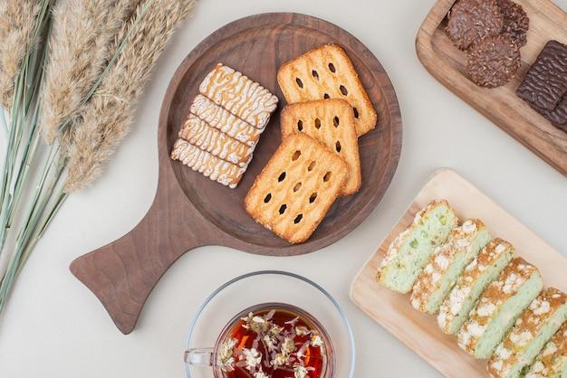 Varias galletas, rebanadas de pastel y una taza de té en la superficie blanca