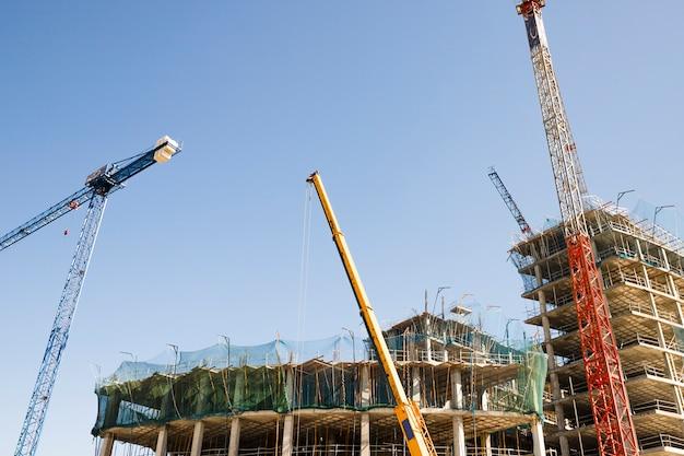 Varias grúas frente a un edificio de construcción contra el cielo azul