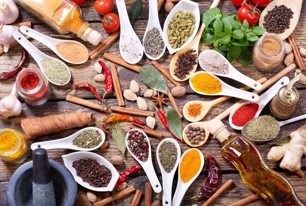 Varias hierbas, especias y verduras para cocinar en la mesa de madera, vista superior