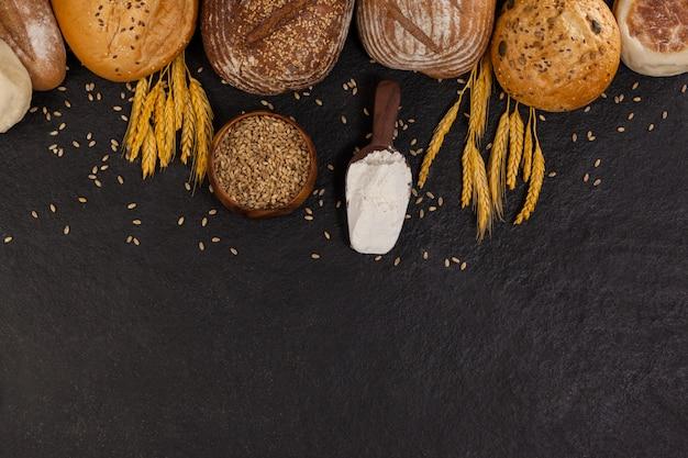 Varias hogazas de pan con harina y granos de trigo