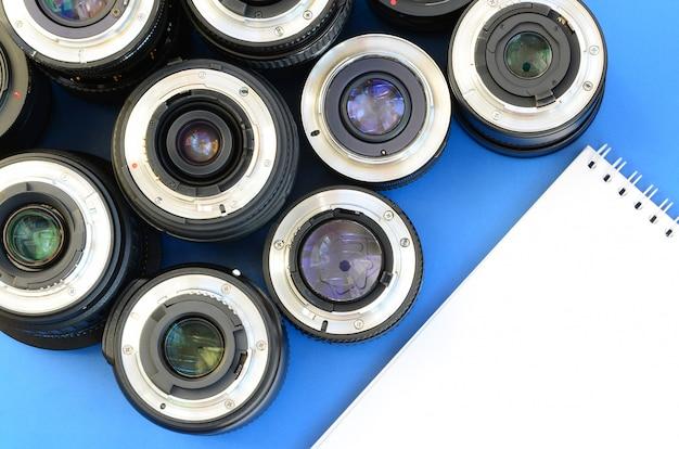 Varias lentes fotográficas y un cuaderno blanco se encuentran sobre un fondo azul brillante. espacio para texto